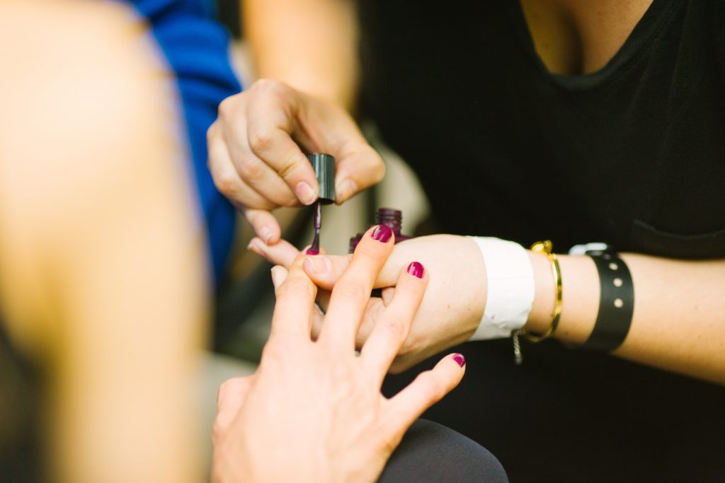 woman getting her fingernails painted