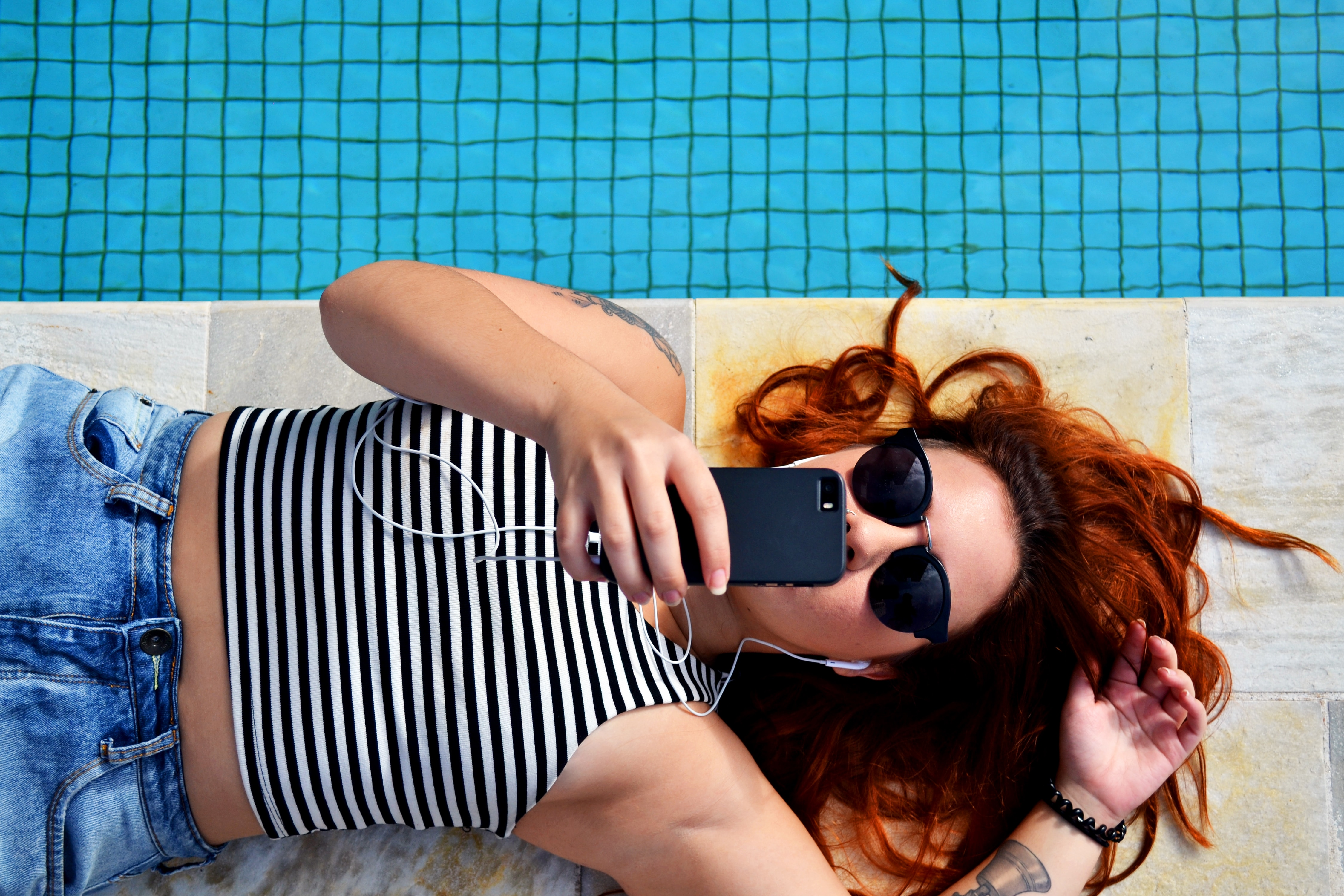 Woman laying by the pool taking a selfie