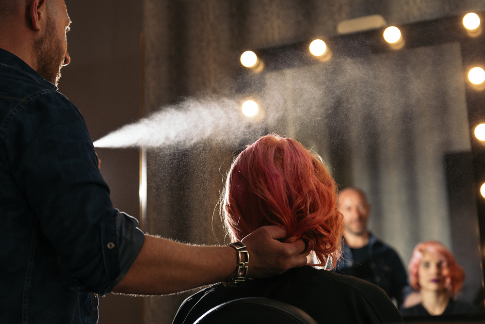 Male hair stylist spraying hairspray on a female client's hairstyle.