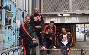 group of four men wearing FUBU brand clothing posing together